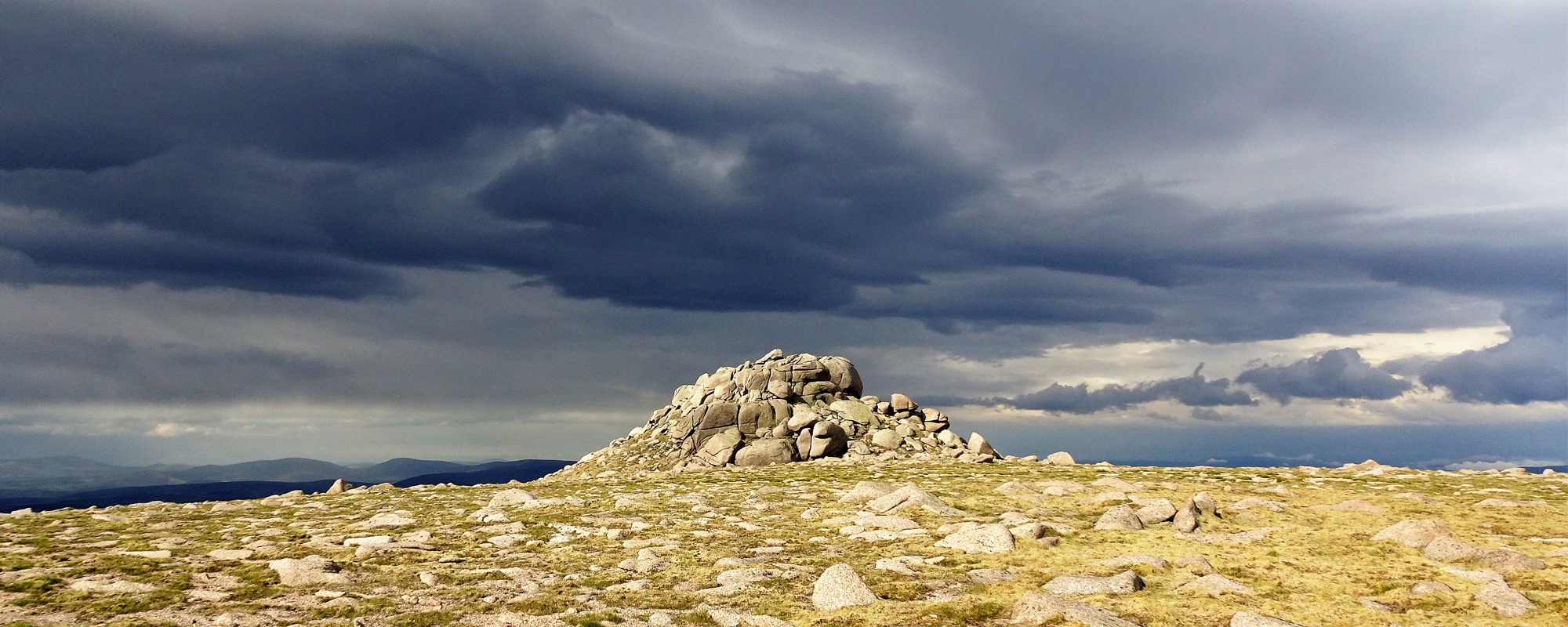The summit of Ben Avon in the Cairngorms bathed in light with a stormy sky