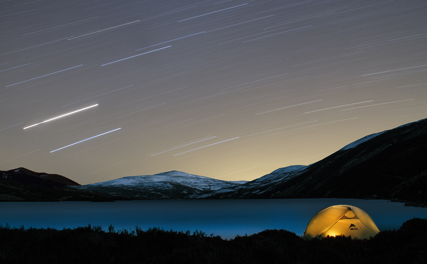 A tent is lit up at night next to a loch in the Cairngorms while star trails fill the sky