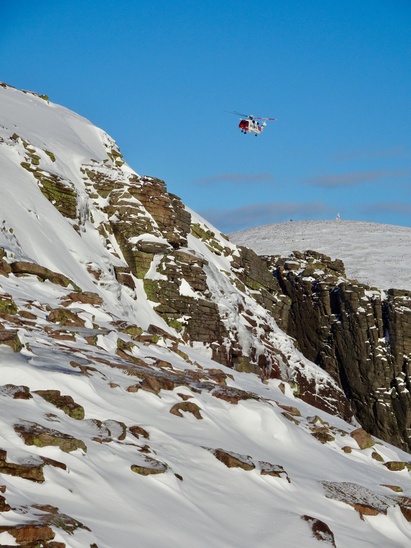 Cairngorm mountain rescue team winch someone to safety from a helicopter just about Loch Avon