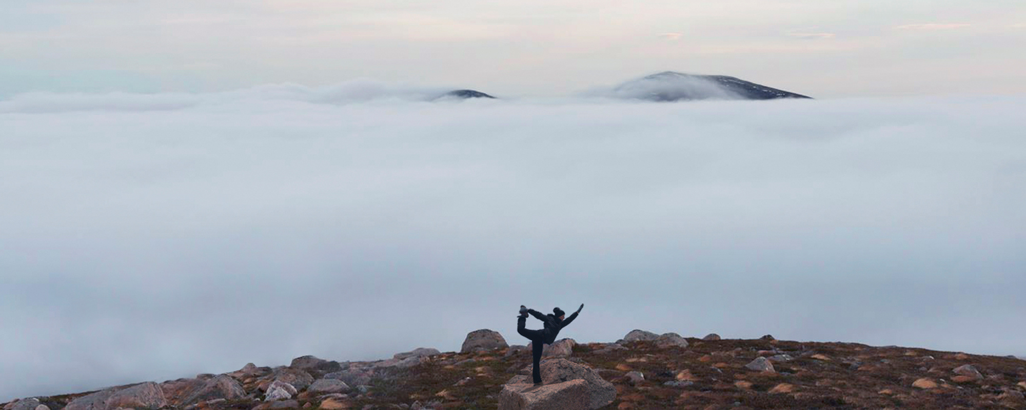 Trekker does a yoga pose on a mountain summit in the Cairngorms