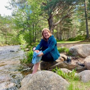Woman sits by river in Caledonian pine forest