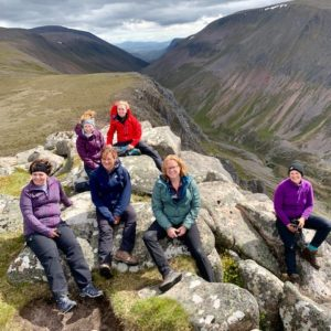 Female trekkers rest in the Cairngorms with views over the Lairig Ghru