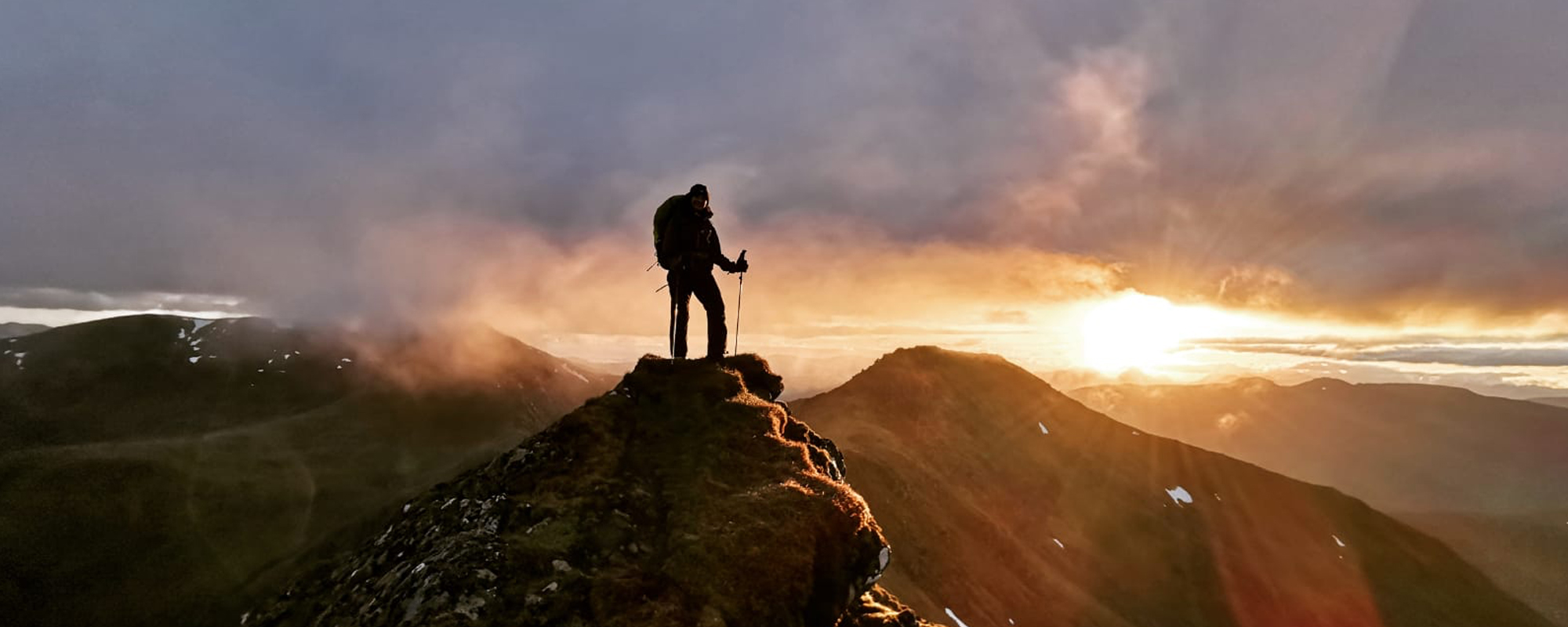 Woman stands on mountain-top at sunset in the Mullardoch mountains, Scotland