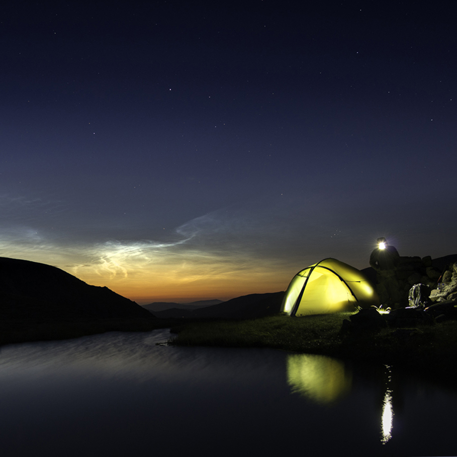 A tent is lit up on a summit in the Cairngorms with noctolucent clouds in the sky